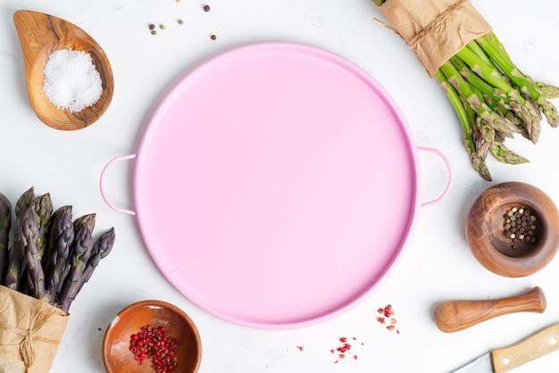 Draufsicht auf trauben von frischem natürlichem bio-spargelgemüse mit verschiedenen gewürzen und rosa platte