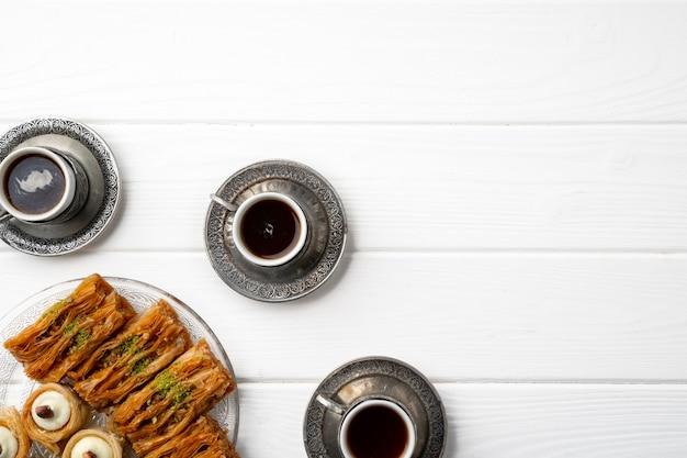 Draufsicht auf türkische süßigkeiten und türkischen kaffee auf weißem holzhintergrund