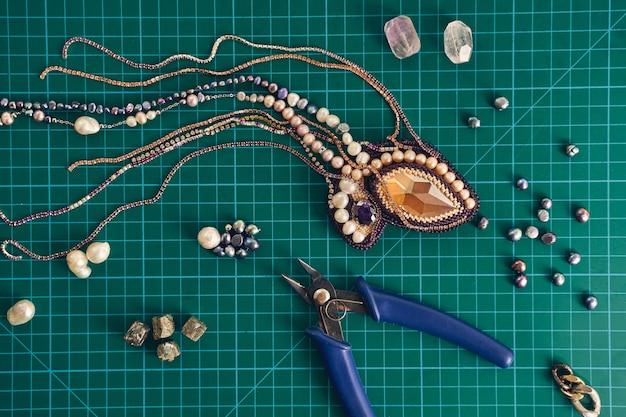 Draufsicht auf türkisfarbene steine, glasperlen, perlen und zangen auf grünem hintergrund