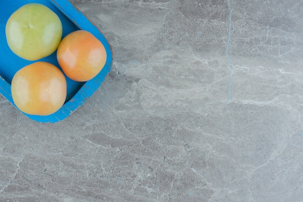 Draufsicht auf unreife tomaten in blauer holzplatte auf grauem hintergrund.