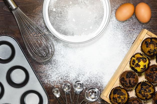 Draufsicht auf vanila, kaffee- und schokoladenmuffins, zutaten: mehl, eier, schneebesen, backen