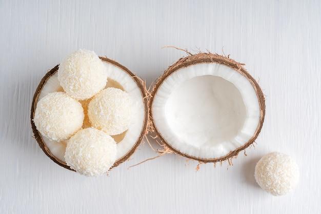 Draufsicht auf vegane kokos-trüffel mit quarkfüllung in halber frischer kokosnuss auf einem tisch