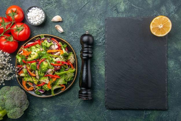 Draufsicht auf veganen salat in einem teller mit verschiedenem gemüse und gabeltomaten mit schwarzem hammerknoblauch-brokolli-blumenschneidebrett auf dunklem hintergrund