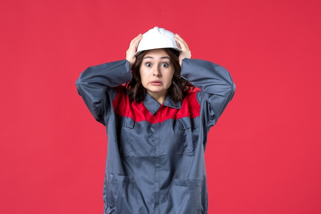 Draufsicht auf verängstigte baumeisterin in uniform mit schutzhelm auf isoliertem rotem hintergrund