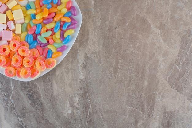 Draufsicht auf verschiedene arten von bunten bonbons auf weißem teller über grauem hintergrund.