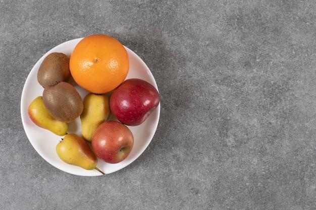 Draufsicht auf verschiedene arten von früchten auf teller