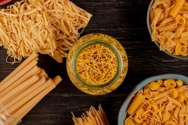 Draufsicht auf verschiedene arten von nudeln als bucatini-spaghetti-fadennudeln-tagliatelle und andere auf holzoberfläche
