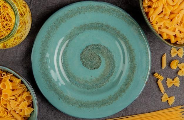 Draufsicht auf verschiedene arten von nudeln in glas und schalen um platte auf grauer stoffoberfläche