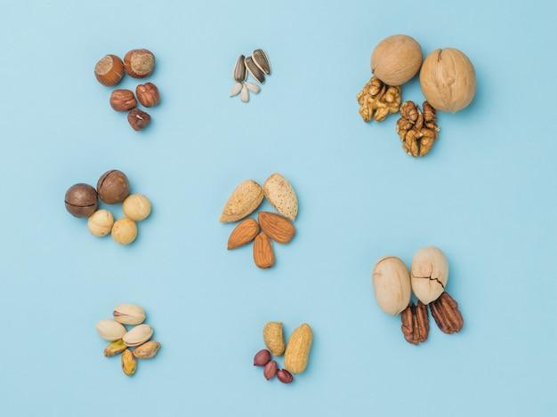 Draufsicht auf verschiedene arten von nüssen auf einem blau. vegetarisches essen.