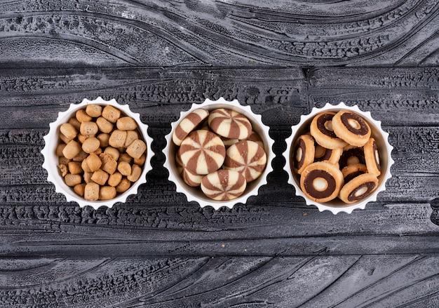 Draufsicht auf verschiedene arten von snacks als coockies und cracker in schalen auf dunkler horizontaler