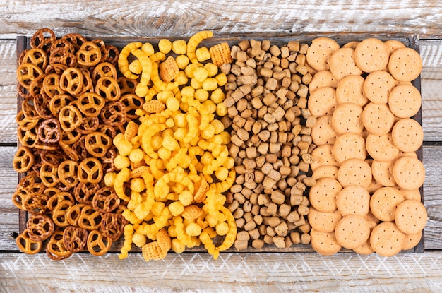 Draufsicht auf verschiedene arten von snacks als cracker und kekse auf weißem holz horizontal