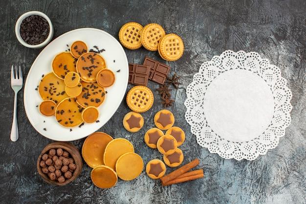Draufsicht auf verschiedene arten von süßigkeiten und ein stück spitze auf grauem grund