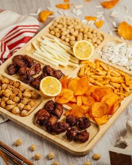 Draufsicht auf verschiedene biersnacks als gebratene dushbara gegrillter hühnerkäse gekochte kichererbsen und kartoffelchips auf einem holzbrett