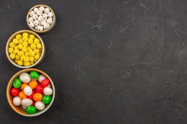 Draufsicht auf verschiedene bunte bonbons in kleinen töpfen auf dunklem hintergrundfarbe
