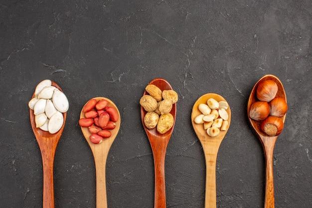 Draufsicht auf verschiedene frische nüsse erdnüsse und andere nüsse auf löffeln auf dunkler oberfläche