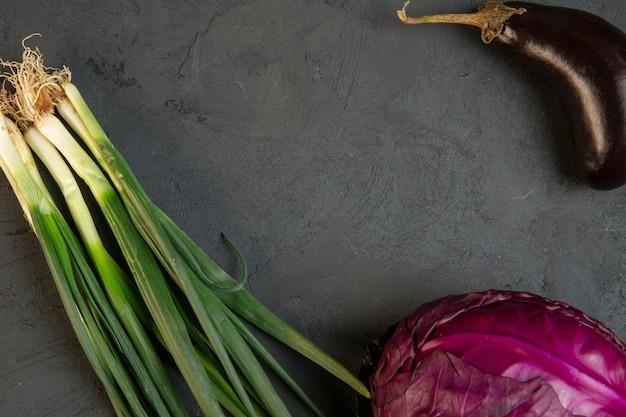 Draufsicht auf verschiedene frischgemüse-rotkohl-auberginen und frühlingszwiebeln mit kopienraum auf dunklem j