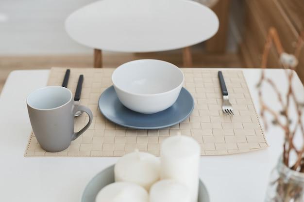 Draufsicht auf verschiedene geschirrteile auf dem weißen esstisch - keramikteller, tasse, gabel, löffel und messer