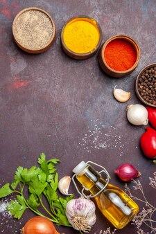 Draufsicht auf verschiedene gewürze mit gemüse auf dunklem tisch