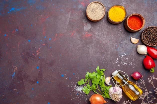 Draufsicht auf verschiedene gewürze mit gemüse auf schwarzem tisch