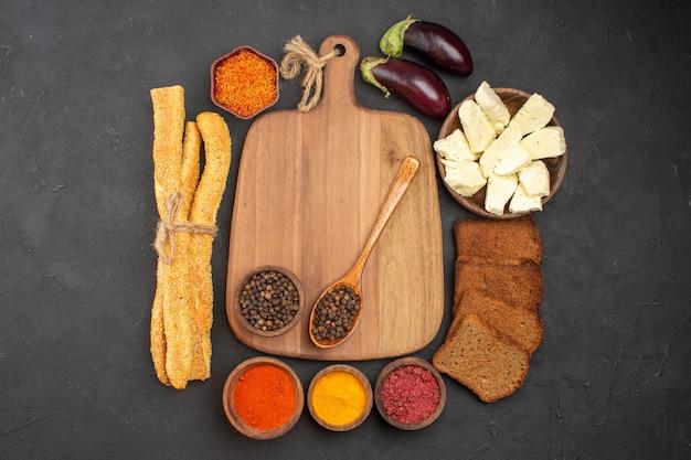 Draufsicht auf verschiedene gewürze mit käse und schwarzbrotlaiben auf schwarz