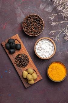 Draufsicht auf verschiedene gewürze mit oliven auf schwarz Kostenlose Fotos