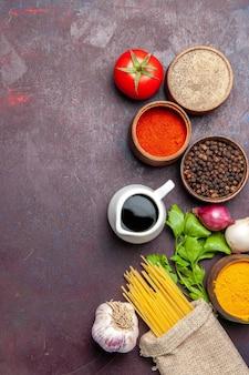 Draufsicht auf verschiedene gewürze mit roher pasta auf schwarzem tisch