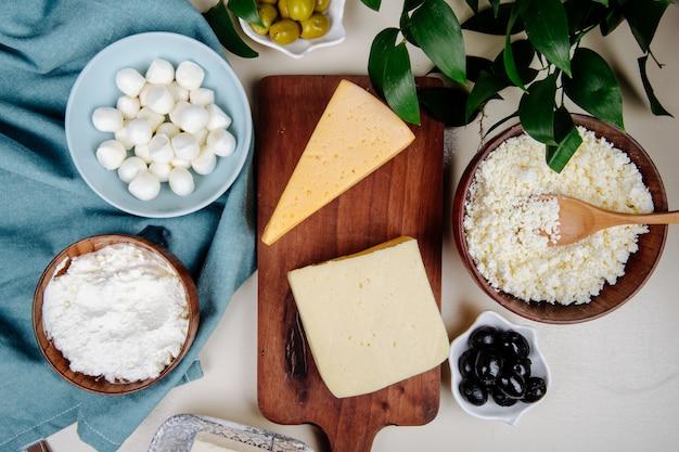 Draufsicht auf verschiedene käsesorten auf holzschneidebrett und hüttenkäse in einer holzschale mit eingelegten oliven auf rustikalem tisch