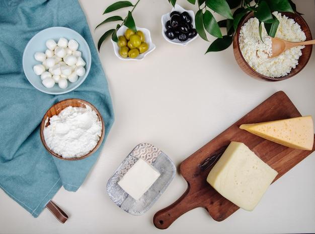 Draufsicht auf verschiedene käsesorten auf holzschneidebrett und hüttenkäse in einer holzschale mit eingelegten oliven auf weißem tisch