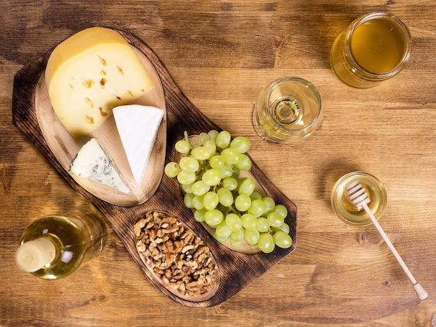 Draufsicht auf verschiedene käsesorten auf holztisch in einem vintage-pub. frische trauben. wein und ein glas wein. leckere walnüsse.