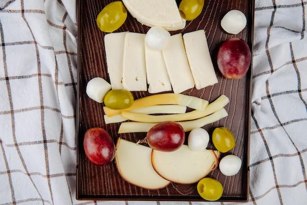 Draufsicht auf verschiedene käsesorten mit eingelegten oliven und süßen trauben auf einem holztablett auf kariertem stoff