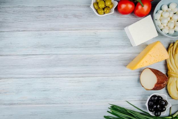 Draufsicht auf verschiedene käsesorten mit frühlingszwiebeln, frischen tomaten und eingelegten oliven auf grauem holztisch mit kopierraum