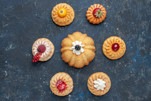 Draufsicht auf verschiedene köstliche kuchen mit sahne und beeren auf dunklem, süßem beerenfrucht-kuchen-keks