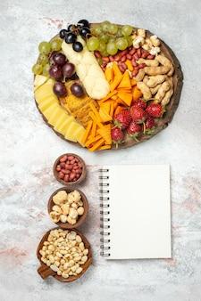 Draufsicht auf verschiedene köstliche snacks frische trauben cips käse und nüsse auf weißer oberfläche