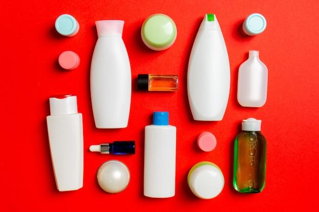 Draufsicht auf verschiedene kosmetische flaschen und behälter für kosmetika auf farbigem hintergrund. flache laienzusammensetzung mit kopienraum.