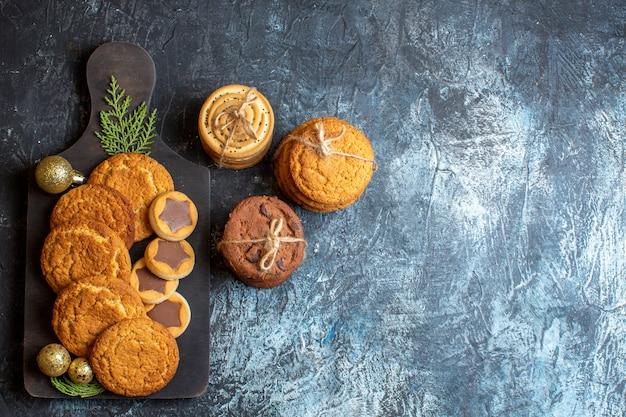 Draufsicht auf verschiedene leckere kekse auf hell-dunklem tisch weihnachten süßes neues jahr zuckerplätzchen tee freier raum