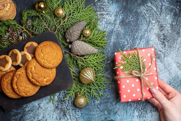 Draufsicht auf verschiedene leckere kekse mit geschenk auf leuchttisch