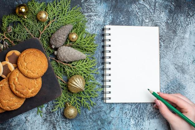 Draufsicht auf verschiedene leckere kekse mit notizblock auf leuchttisch