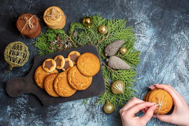 Draufsicht auf verschiedene leckere kekse mit spielzeug und zapfen auf leuchttisch
