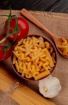 Draufsicht auf verschiedene makkaroni-arten in der schüssel mit holzlöffel tomaten vom typ fadennudeln und knoblauch auf sackleinen und holzoberfläche