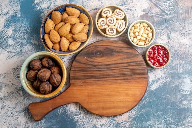 Draufsicht auf verschiedene nüsse mit confitures und marmelade auf heller oberfläche