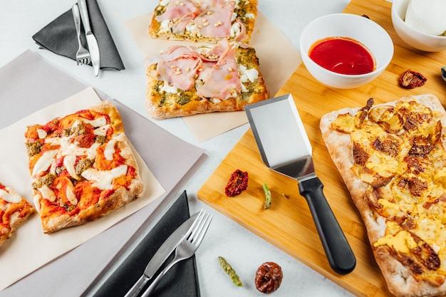 Draufsicht auf verschiedene pizzastücke mit einer soße