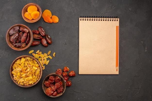 Draufsicht auf verschiedene rosinen aus trauben mit getrockneten aprikosen auf der grauen oberfläche