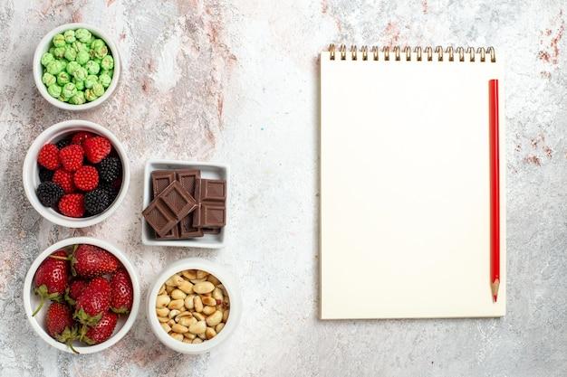 Draufsicht auf verschiedene snacks erdnussbeeren und bonbons auf hellweißer oberfläche