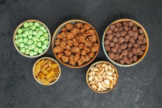 Draufsicht auf verschiedene süße bonbons mit nüssen auf grau