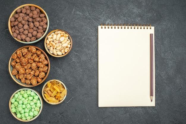 Draufsicht auf verschiedene süße bonbons mit nüssen und rosinen auf grau