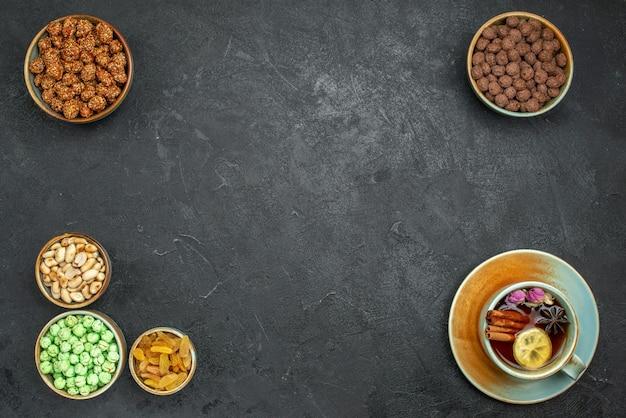 Draufsicht auf verschiedene süße bonbons mit nüssen und tasse tee auf grau