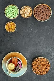 Draufsicht auf verschiedene süße bonbons mit nüssen und tee auf schwarzem grau