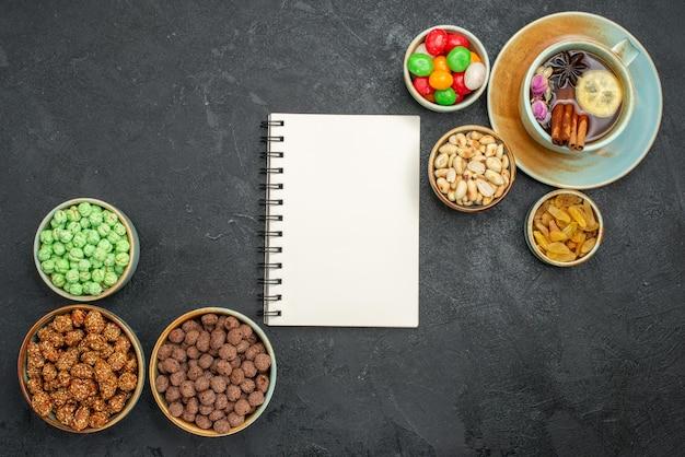 Draufsicht auf verschiedene süße bonbons mit tasse tee auf grau