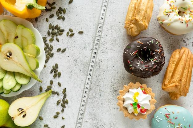 Draufsicht auf verschiedene süße speisen; frisches obst mit gemüse und maßband