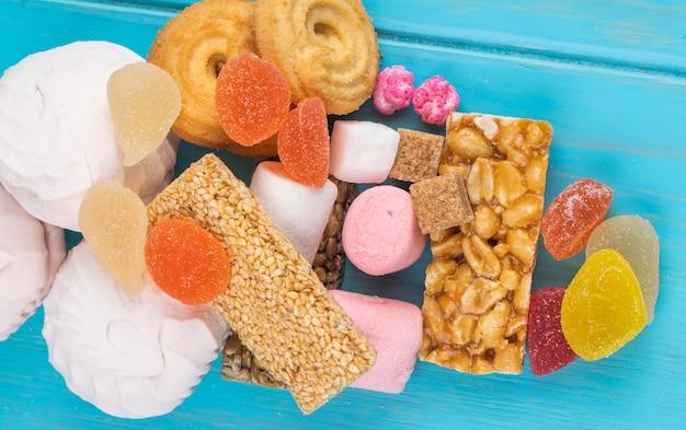 Draufsicht auf verschiedene süßigkeiten kozinaki marshmallow marmelade bonbons und kekse auf blau